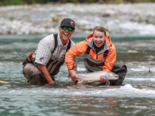smiling with a big bull trout in her hands