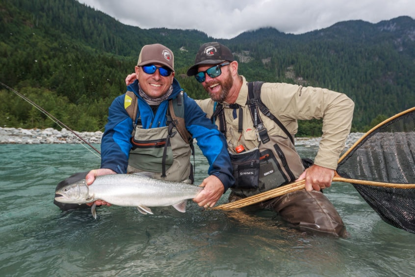 happy fly fishing guide and client with a bull trout
