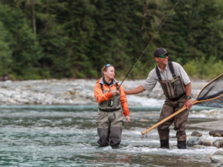 Guide and fly fishing angler having fun