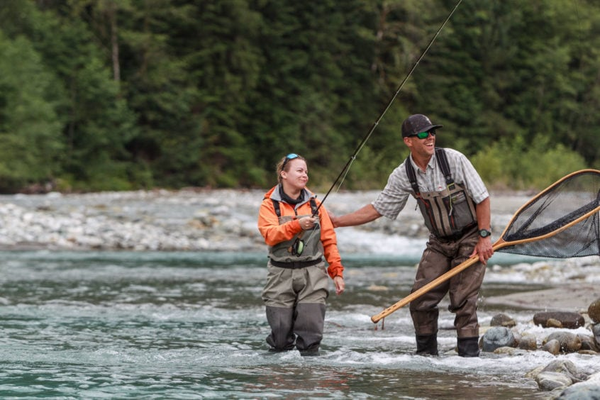 Guide and fly fishing angler having fun
