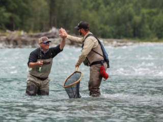 Angler and guide giving a high five after landing a nice fish