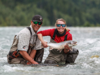 Two anglers holding a large bull trout on the Pitt River